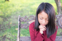 a girl praying sitting on a park bench