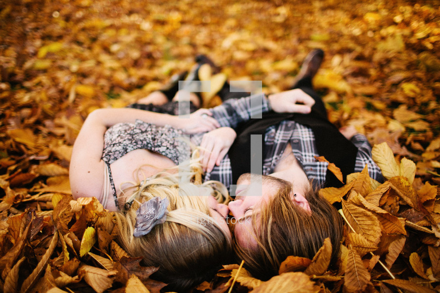 couple lying in a pile of leaves