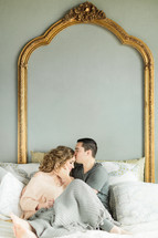 A man kisses a woman's forehead.