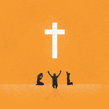 Three people worshipping before a large white cross.