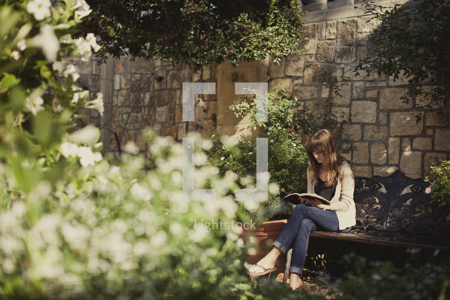 Woman reading bible on bench in garden,