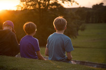 kids sitting on a wall looking out at a green pasture
