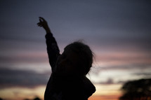 silhouette of a reaching arm