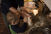 a toddler boy helping in the kitchen