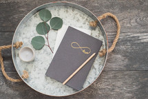 tray with votive candle, journal, pencil, and eucalyptus twig