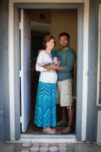 New parents holding their infant child while standing in the doorway.