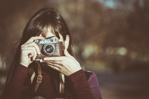 a woman with a vintage camera taking a picture
