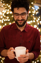 a man holding a mug of hot cocoa standing in front of a Christmas tree