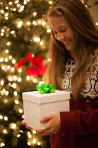 a woman holding a Christmas gift standing in front of a Christmas tree