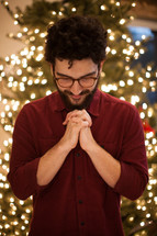 a man with head bowed in prayer standing in front of Christmas tree