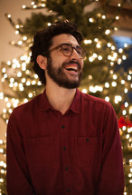 a smiling man standing in front of a Christmas tree