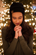 a woman praying in front of a Christmas tree
