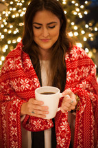 a woman wrapped in a blanket holding a mug in front of a Christmas tree