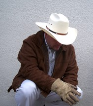 A neatly dressed cowboy getting ready for the workday by kneeling and praying.