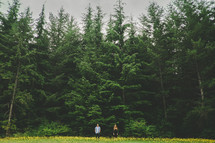 man and a woman standing in a meadow in front of a forest