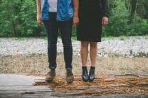 Man and woman standing on a log.
