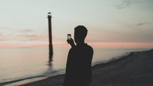 a man taking a picture of water lapping onto a shore at sunset