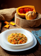 Pumpkin risotto, recipe with rice and pumpkin on rustic table with ingredients. Autumn and Halloween recipe.