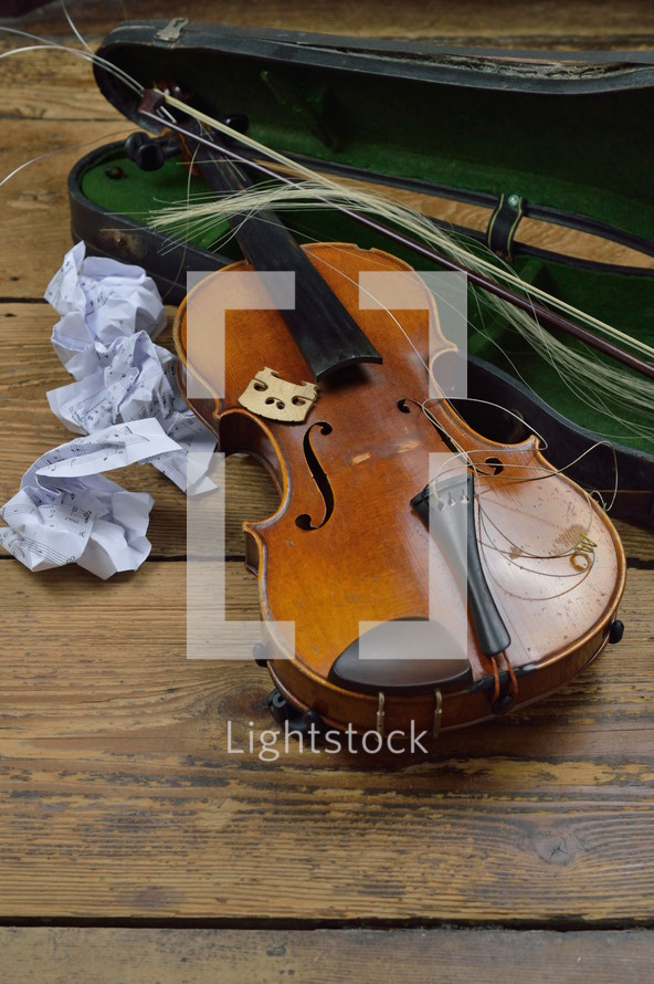 old broken violin on rural wooden floor with antique violin case and tattered fiddlestick