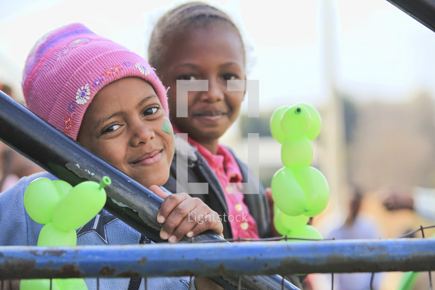 Little girls smiling and holding balloons