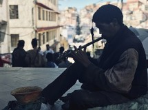 a man playing a flute on the street in Nepal