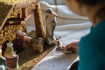 child playing with a nativity scene