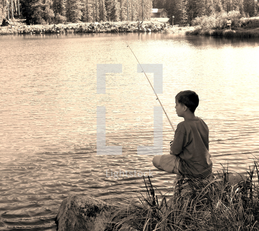 boy fishing on the shore of a lake