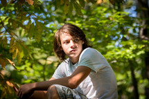 teen boy squatting in a forest