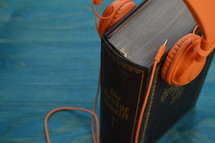 old german bible with modern orange headphones on teal wooden background