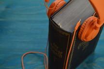 old german bible with modern orange headphones on teal wooden background