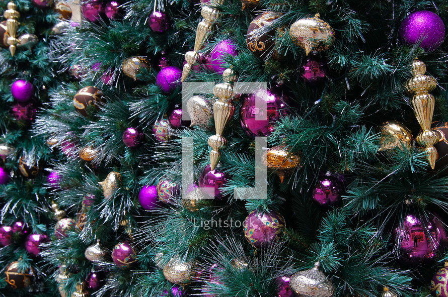 Purple and gold ball Christmas ornaments hanging from pine Christmas tree.