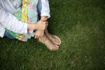 A woman in sandals sits in green grass.