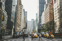 people crossing a crosswalk in front of yellow cabs in NYC