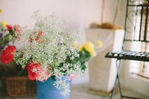 Bouquet of flowers in a vase near a chair.