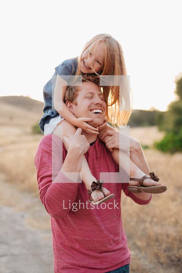 a father with his daughter on his shoulders