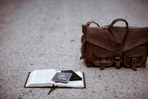 passport and phone on an opened Bible on a gravel road