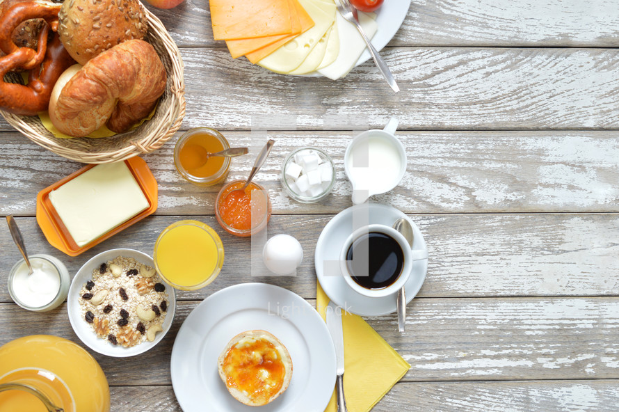 breakfast table with lots of fresh food like coffee, rolls, cheese, sausages, eggs, orange juice, jam, butter and a basket full of croissant, rolls and pretzel with copy space to the right