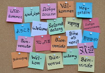 welcome in various languages on a cork board
