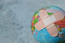 bandaids on a globe - healing the world