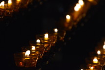 many lit candles in a dark church.  candle, lit, flame, fire, burning, candles, flames, kindled, light, lighted, blaze, blazing, burning, burn, many, much, lot, dark, lighten, brighten, bright, illuminate, illumine, shine, shining, see, seeing, show, showing, symbol, symbolic, symbolize, symbolizing, believe, believers, wax, church, pray, prayer, votive, darkness, burnt, donation, donate, ceremony, offering, offer, yellow, white, orange, row, line, lines, unlit, rows, commemorate, remember, recall, remembrance, memory, memento, think of, sign, creed
