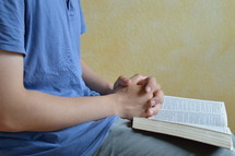 man praying with a Bible in his lap