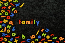 the word FAMILY written with colorful magnetic letters on black ground.