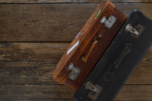 two old weathered suitcases on a rustic wooden floor