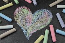 heart shape in sidewalk chalk on slate surrounded with sticks of chalk