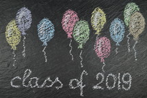 chalk on slate with balloons and the words: class of 2019