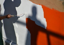 man painting over a red wall