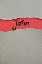 John - torn open kraft paper over light red paper with the name of the Gospel of John