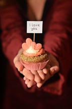Woman offering a cupcake with pink hearts and a sign saying I LOVE YOU.