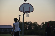 teens playing basketball at sunset