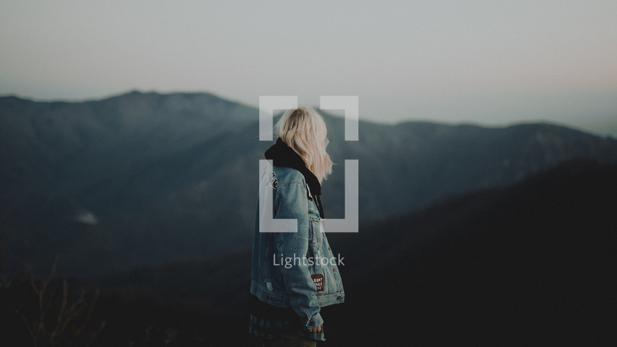 a woman in a jean jacket standing on a mountaintop